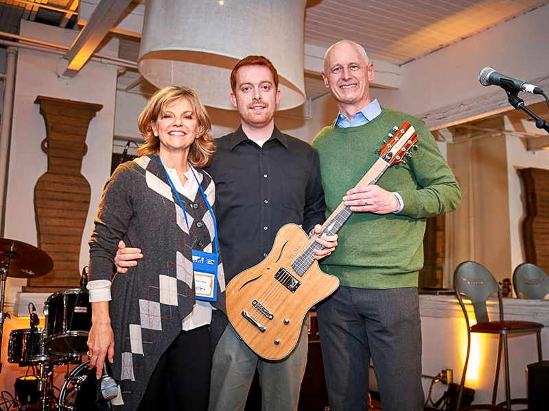 Kathy McKeil, luthier Daniel Clark and Steve Fletcher pose with the custom McKeil 60th Anniversary Guitar, MicMac1956, by Cithara Guitars Inc.