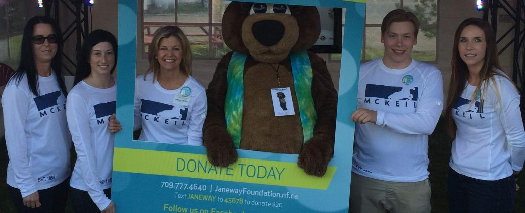 McKeil crew and family pose with Sunny Bear at the Janeway Telethon.