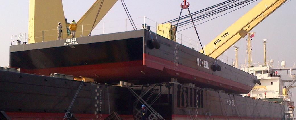 A yellow crane on the MM 143 barge.
